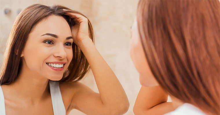 A woman looking into the mirror and wondering how long will teeth whitening last from 16TH AVENUE DENTAL